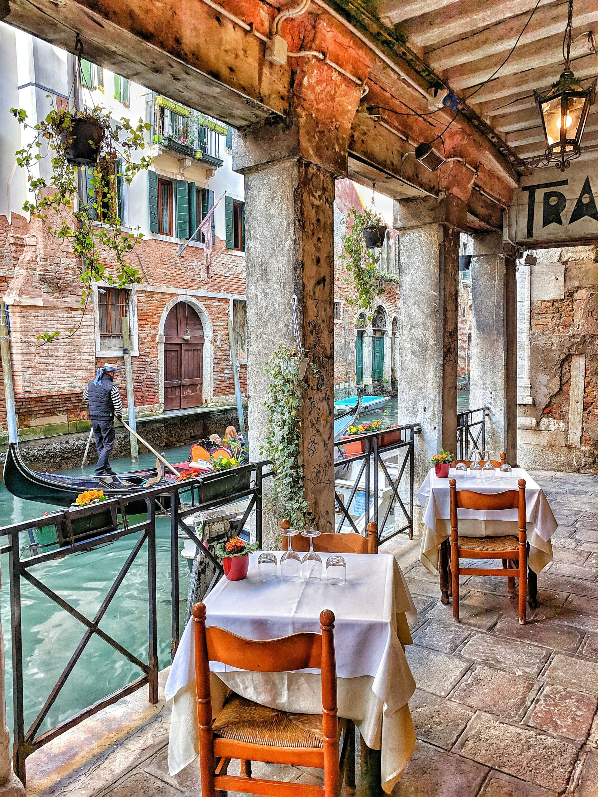Italy - People riding in a boat passing by a restaurant in Venice